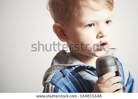 little boy singing in microphone.child in karaoke.music.4 years old - stock photo