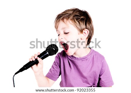 little boy singing through a microphone