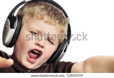 Little boy singing, wearing headphones - stock photo