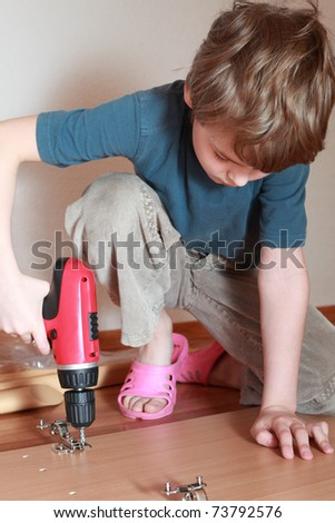 Little boy sit down on knee on the floor and diligently tightening screws in wooden board - stock photo