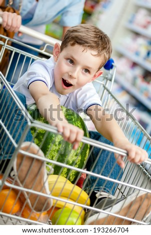 Little boy sits in the cart with watermelon and other products bought by parents - stock photo