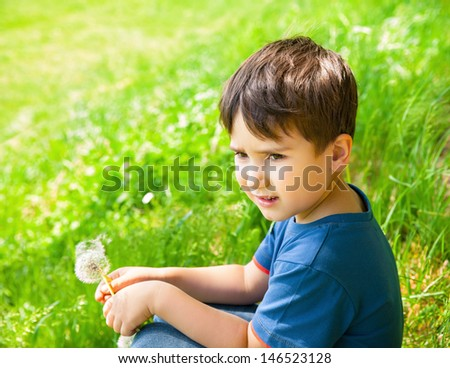 Little boy sits in the meadow on a sunny day and holding dandelion - stock photo