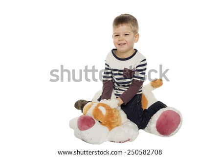 little boy sits on a toy dog on a white background