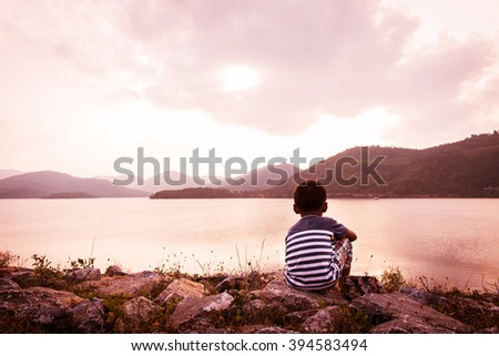 little boy sitting alone at dam in the evening  - stock photo