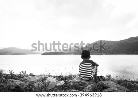 little boy sitting alone at dam in the evening ,black and white tone - stock photo