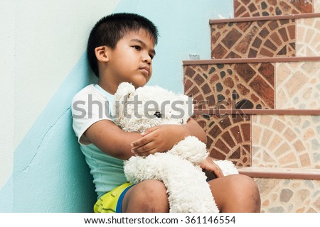 little boy sitting alone at staircase in the park - stock photo
