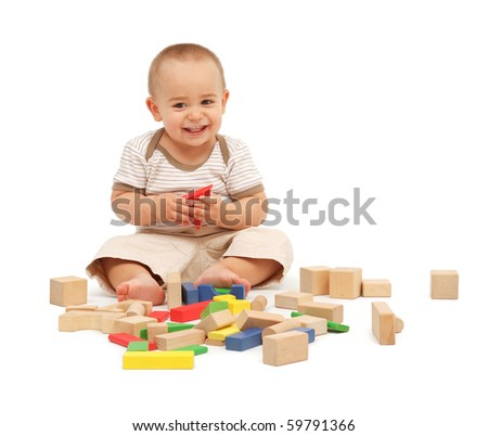 Little boy sitting and playing with colorful wooden blocks - stock photo