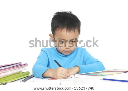 Little boy sitting and writing in notebook. Isolated on white background