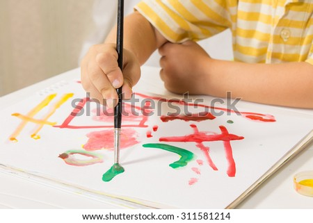 Little boy sitting at a table paints a picture of a white sheet