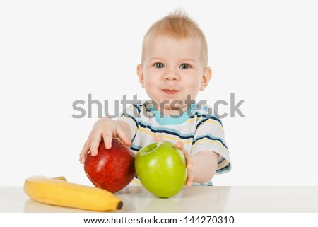 Little boy sitting at a table with fruit - stock photo
