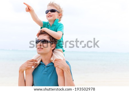 little boy sitting at his father shoulders at pointing at something with his finger - stock photo