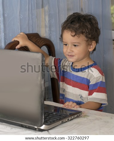 little boy sitting at the laptop at home