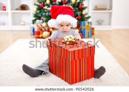 Little boy sitting behind big Christmas present box - stock photo