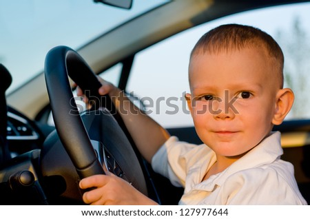 Little boy sitting behind the wheel of a car in evening light with a lovely smile on his face - stock photo
