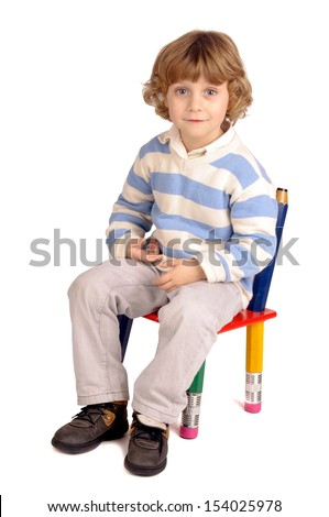 little boy sitting in a chair - stock photo
