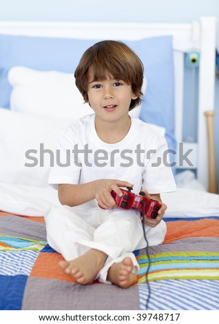 Little boy sitting in bed playing videogames