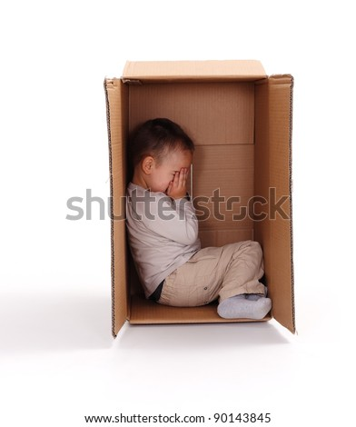 Little boy sitting in cardboard box, hiding his face with hands - stock photo