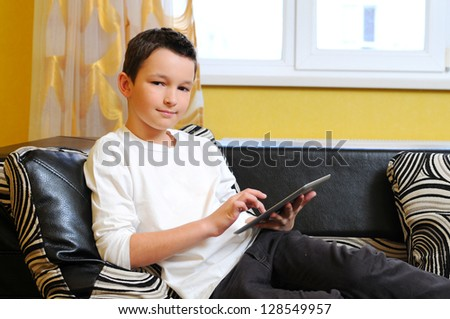 Little boy sitting in sofa with electronic tablet