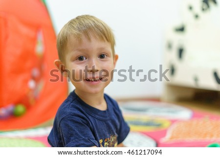Little boy sitting in the children's room, home. Portrait of a child three years.