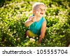 Little boy sitting in the grass picking clover with a cute expression on his face - stock photo