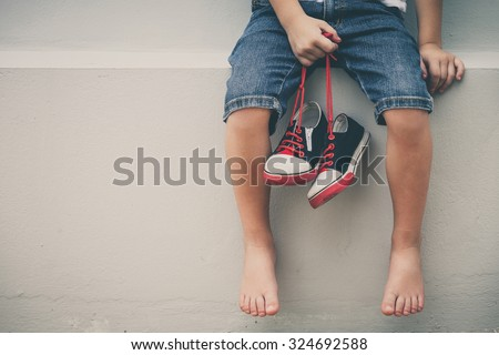 Little boy  sitting near the house and keeping the youth sneakers in his hands of at the day time. - stock photo