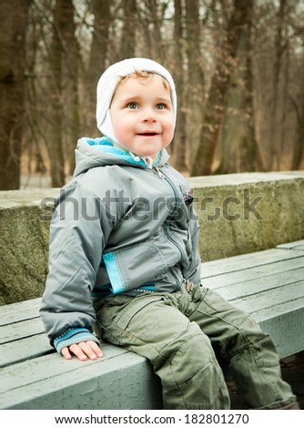 little boy sitting on a bench in the park - stock photo