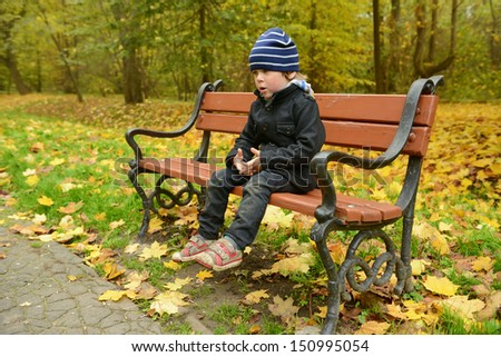 Little boy sitting on a bench in the park in autumn