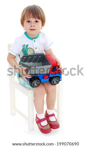 little boy sitting on a chair and holding a toy car. Isolated on background. - stock photo