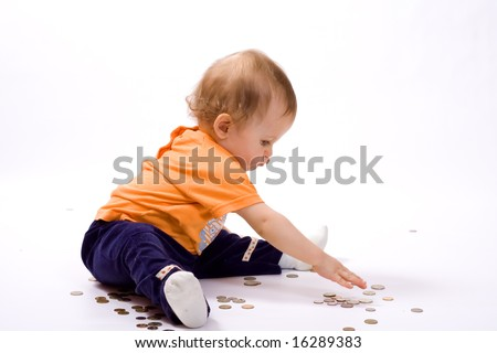 Little boy sitting on a floor sideways to a viewer and playing with a lot of coins