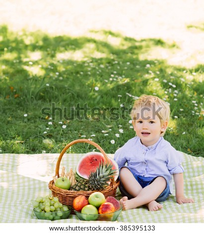 Little boy sitting on a mat having a picnic with a basket full of fruits.