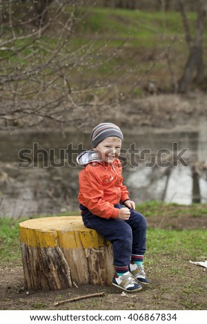 Little boy sitting on a stump in the spring park. Baby boy in orange jacket, outdoors - stock photo
