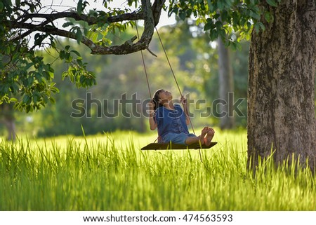 Little boy sitting on a swing.