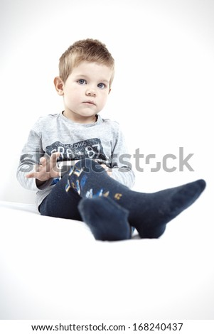 Little boy sitting on bed at home