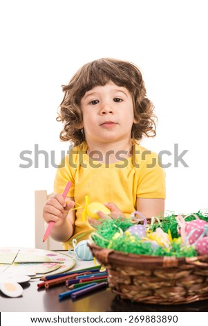 Little boy sitting on chair and painting Easter eggs isolated on white background - stock photo
