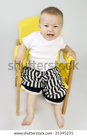 Little boy sitting on chair in striped pants