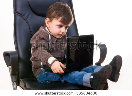 little boy sitting on chair with laptop