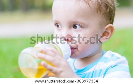 Little boy sitting on grass and drinking his beverage at the end of the funny hot summer day - stock photo
