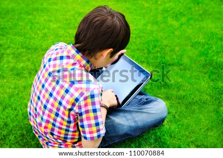 Little boy sitting on grass and using tablet computer - stock photo