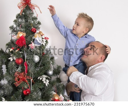 little boy sitting on his father's hands and decorate the Christmas tree together - stock photo