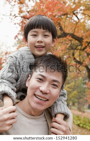 Little boy sitting on his fathers shoulders, walking through the park in autumn, Close up portrait - stock photo