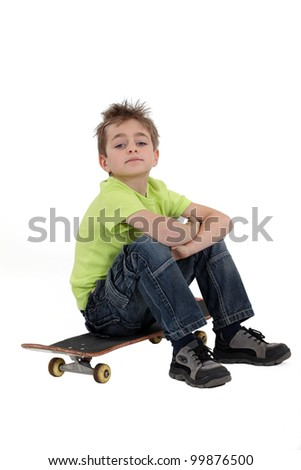 little boy sitting on his skateboard - stock photo