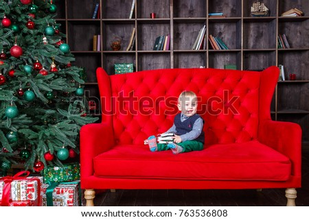 Little boy sitting on sofa at Christmas, New Year