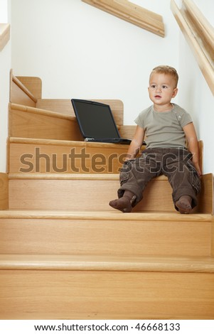 Little boy sitting on stairs, playing with laptop computer.