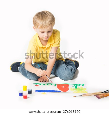 Little boy sitting on the floor and painting