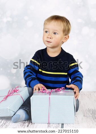 Little boy sitting on the floor and unwrapping christmas presents - stock photo