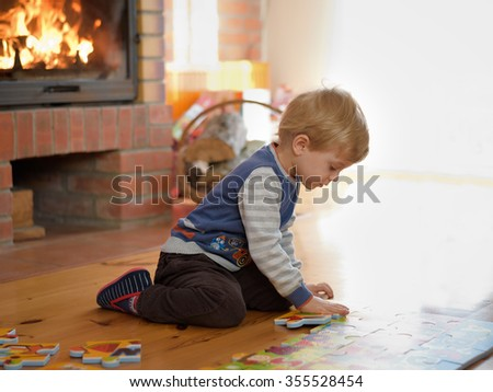 little boy sitting on the floor making puzzles - stock photo