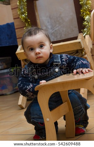 little boy sitting on the floor near the wooden chairs
