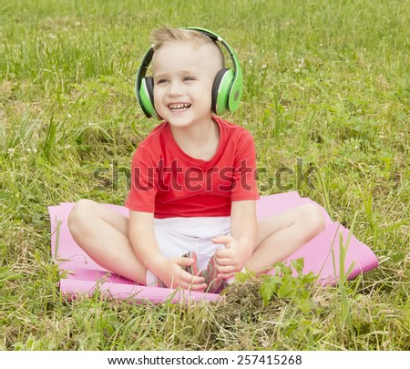 little boy sitting on the grass in the earpiece and laughs - stock photo
