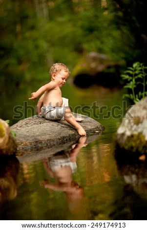 little boy sitting on the stone near the forest lake