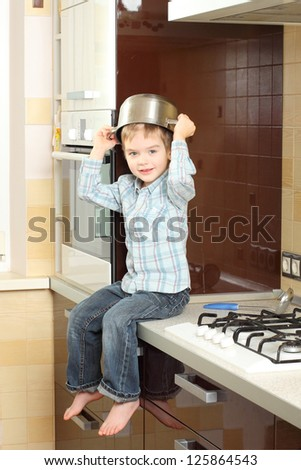 little boy sitting on the table with a pot on his head